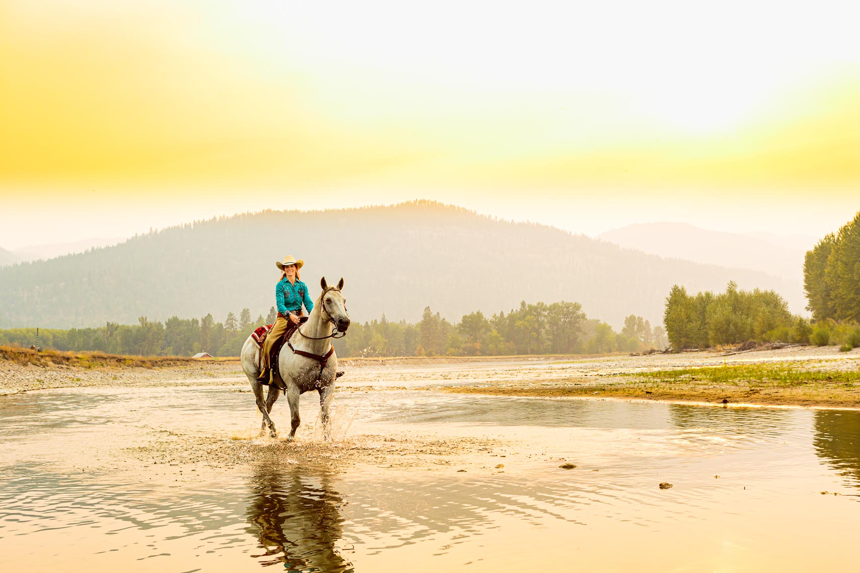 Cowgirl Riding Horse in River | Photographer Michael DeYoung